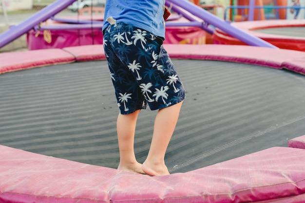 Jongen die op een trampoline springt die door kabels bij een markt wordt geholpen.