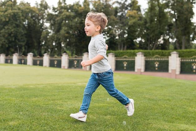 Jongen die op gras loopt