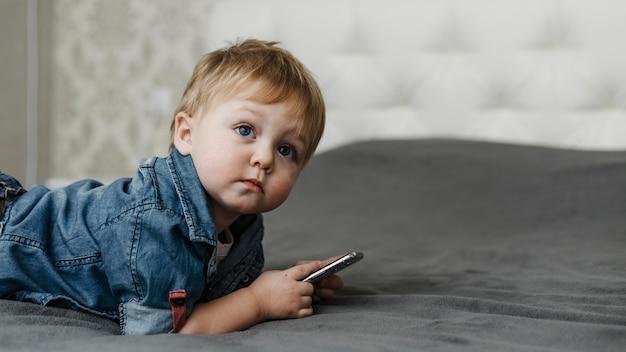 Jongen die op het bed legt en mobiele telefoon houdt