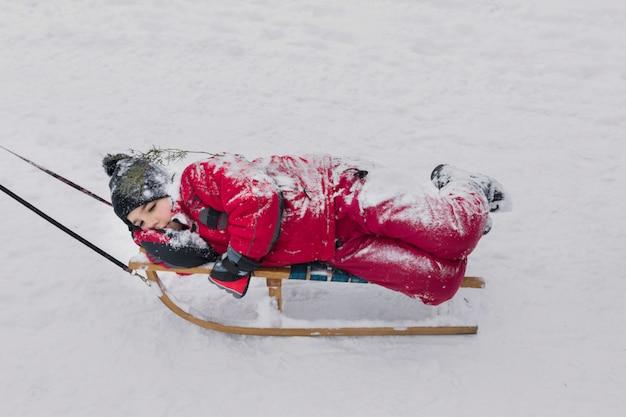 Jongen die op houten slee op sneeuwlandschap bij wintertijd ligt