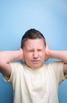 Jongen die oren bedekt met de hand die moe is, hoofdpijn, echte emotie toont. niet geluisterd.gesloten oren