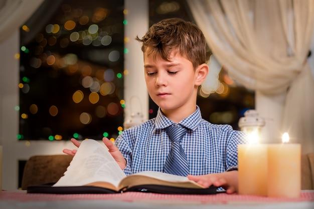 Jongen die pagina van boek draait. kind en boek bij kaarslicht. hij heeft de helft gelezen. enorme verzameling gedichten.