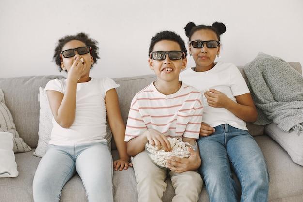 Jongen die popcorn eet. jongen afrikanen in een glas. kijken naar een kinderfilm.