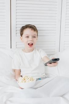 Jongen die popcornzitting in bed eet en op tv let Premium Foto