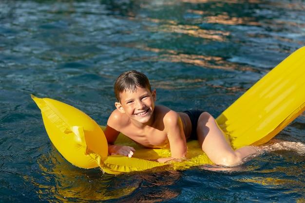 Jongen die pret heeft bij het zwembad met poolvlotter