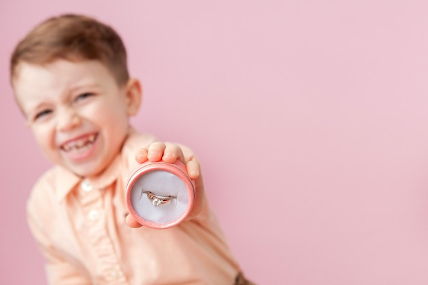 Jongen die ring in doos op roze achtergrond geeft