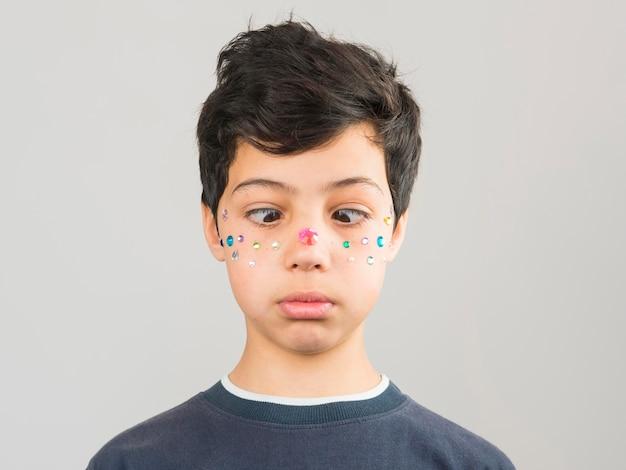 Jongen die samenstellingsparels op zijn gezicht heeft