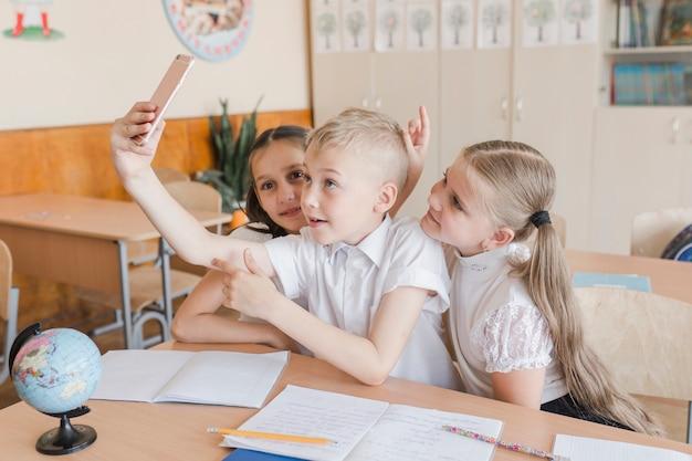 Jongen die selfie met meisjes bij bureau nemen
