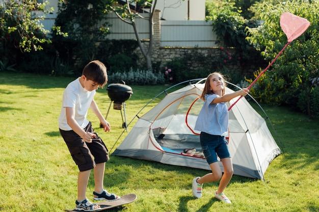 Jongen die skateboard speelt dichtbij zijn zuster die vlinders en insecten met haar schepnet vangt