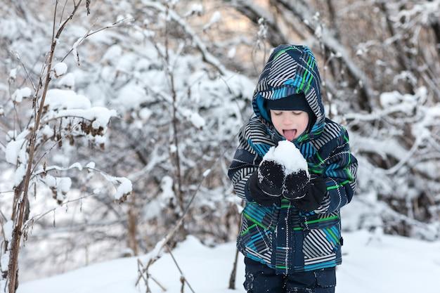 Jongen die sneeuw in de winter eet.
