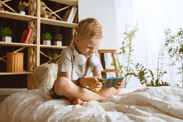 Jongen die thuis verschillende gadgets gebruikt. klein model met slimme horloges, smartphone of tablet en koptelefoon.