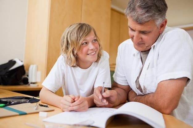 Jongen die thuiswerk met zijn vader doet