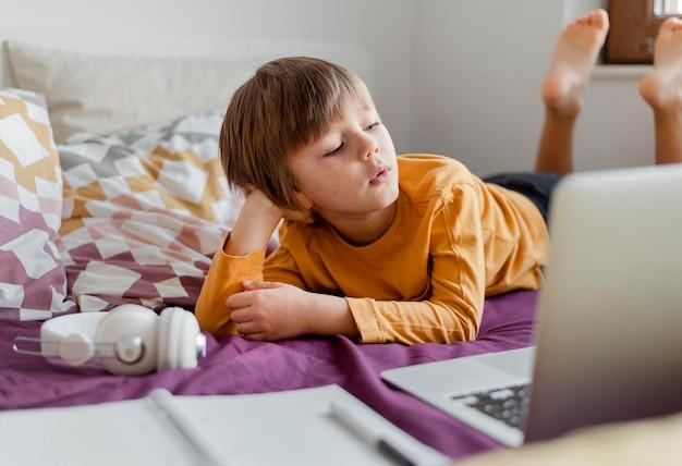 Jongen die van zijn laptop virtuele klassen leert