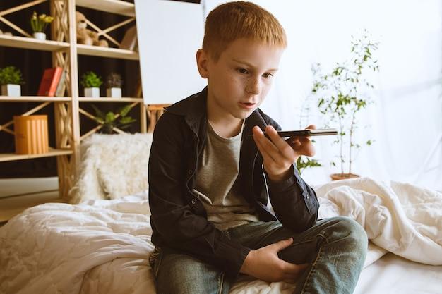 Jongen die verschillende gadgets thuis gebruikt. klein model met slimme horloges, smartphone of tablet en koptelefoon. selfie maken, chatten, gamen, video's kijken. interactie van kinderen en moderne technologieën.