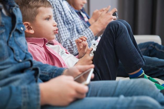 Jongen die videospelletjes speelt dichtbij gewassen broers en zussen
