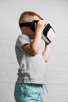 Jongen die virtuele hoofdtelefoon thuis met behulp van
