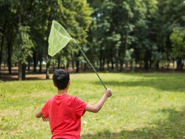 Jongen die vlinders in het park probeert te vangen