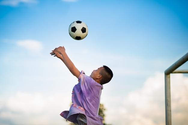 Jongen die voetbal speelt als een keeper die goed kan bewegen