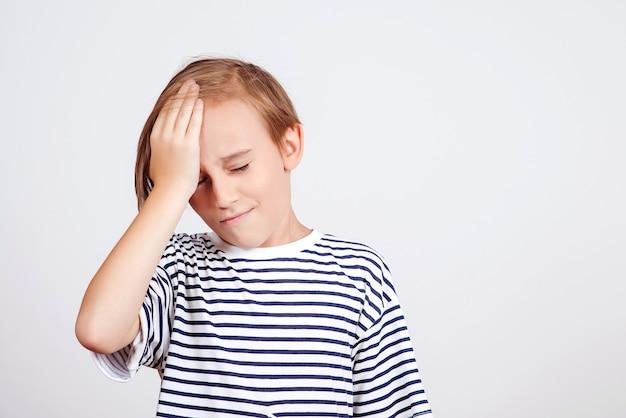 Jongen die voorhoofd met palm slaat en ogen sluit. ongelukkig kind dat iets vergeet. zie emotie en expressie onder ogen. oeps, wat heb ik gedaan. terug naar school en nieuws. oh nee. jongen die over fouten denkt.