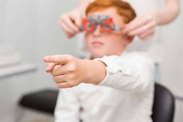 Jongen die wijsvinger naar camera richt terwijl het hebben van oogtest in optiekkliniek