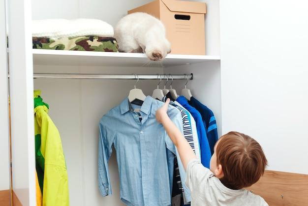 Jongen die zich door garderobe met kleren bevindt. leuke jongen die schooloverhemd neemt om te dragen. kid organiseren van kleding in kledingkast.