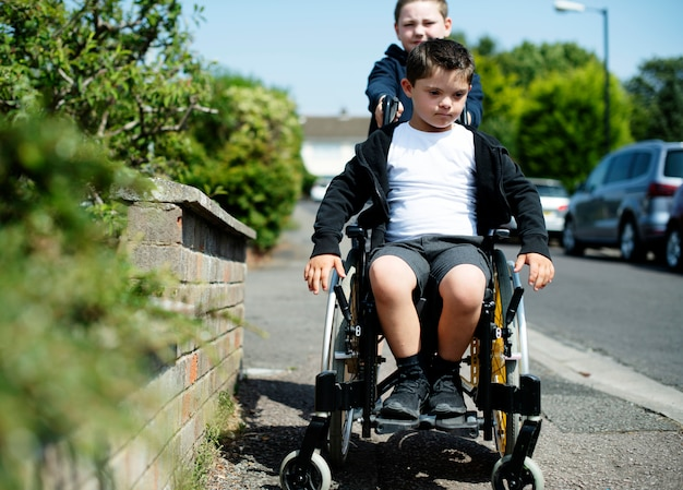 Jongen die zijn broer in een rolstoel duwt