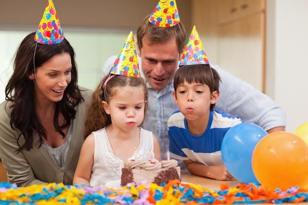 Jongen die zijn kleine zuster helpt om de kaarsen op haar verjaardagscake uit te blazen