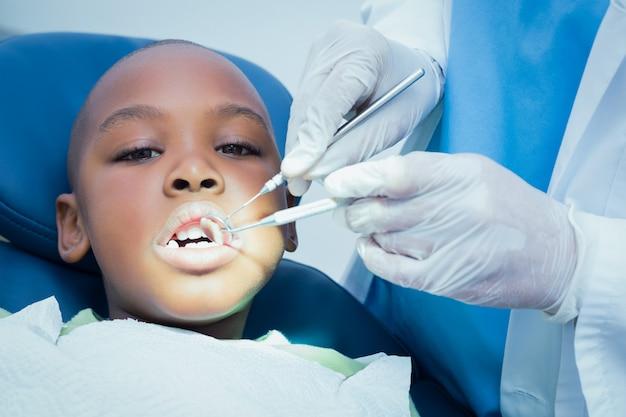 Jongen die zijn tanden heeft die door tandarts worden onderzocht