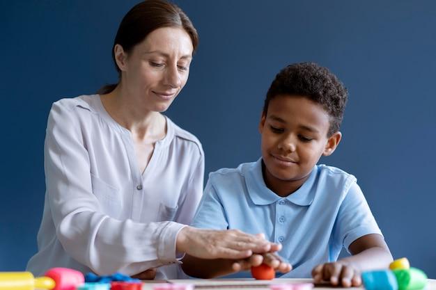Jongen doet een ergotherapiesessie met een psycholoog