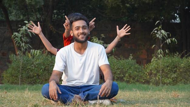 Jongen doet meditatie en kinderen spelen and