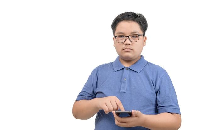 Jongen draagt een bril en raakt de mobiele telefoon aan op het scherm geïsoleerd op een witte achtergrond, kinderen verslaafd aan het concept van mobiele telefoonspellen