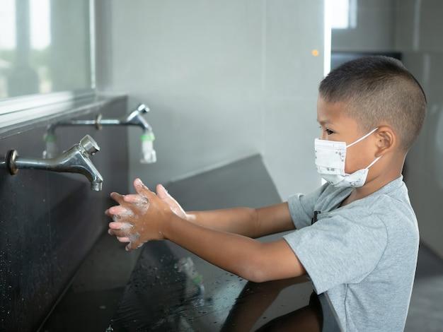 Jongen draagt ?? een masker wassen handen in openbare toiletten