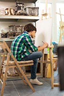 Jongen draagt een spijkerbroek die het druk heeft tijdens het tekenen op de kunstacademie