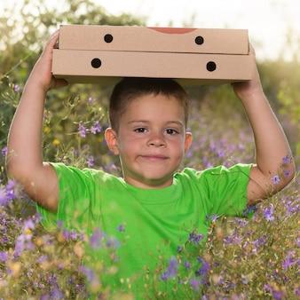Jongen draagt twee dozen pizza op zijn hoofd en lacht in een bloemrijk veld