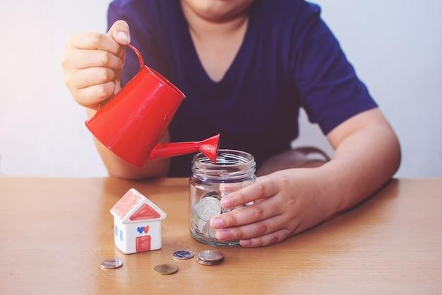 Jongen drenken huis en munten. plan voor huisconcept