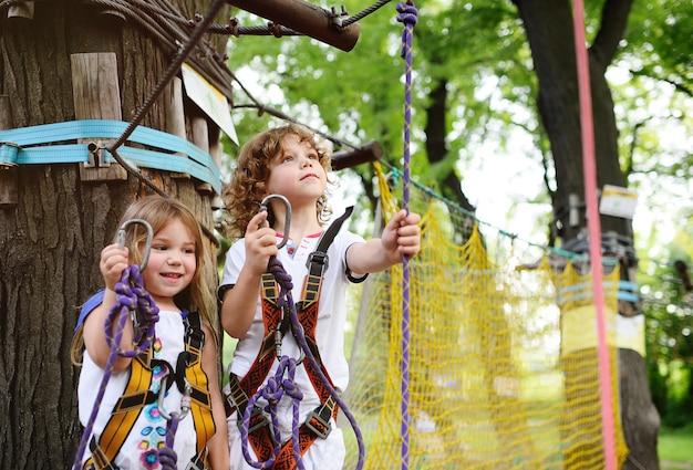 Jongen en een meisje in een avonturenpark houden zich bezig met rotsklimmen of passeren obstakels op de kabelbaan.