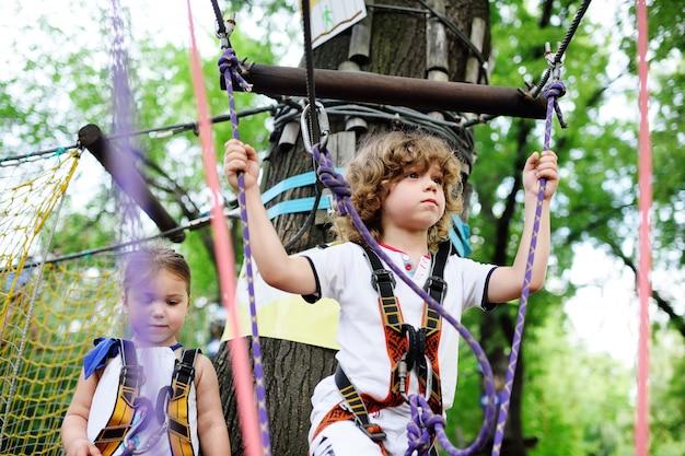 Jongen en een meisje in het touwpark passeren obstakels.