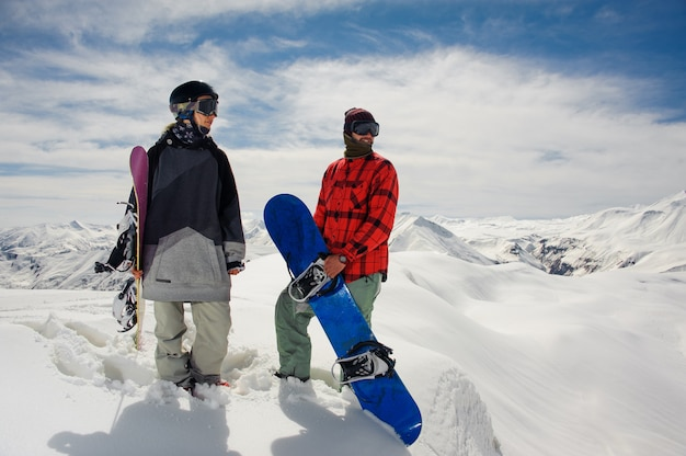 Jongen en een meisje in warme kleren staan met snowboards tegen de bergtoppen