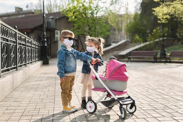 Jongen en een meisje lopen met een kinderwagen in beschermende gezichtsmaskers