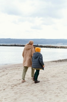 Jongen en grootmoeder bij strand volledig schot