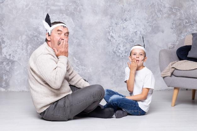 Jongen en grootvader spelen indianen op een grijze muurmuur. senior man en kleinzoon spelen injun in de woonkamer. familie samen