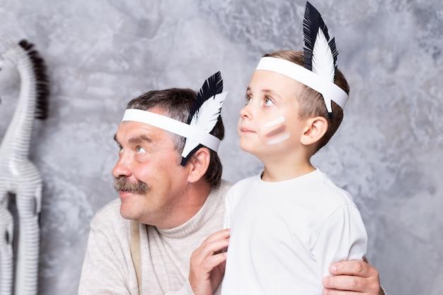 Jongen en grootvader spelen indianen op een grijze muurmuur. senior man en kleinzoon spelen injun. portret close-up