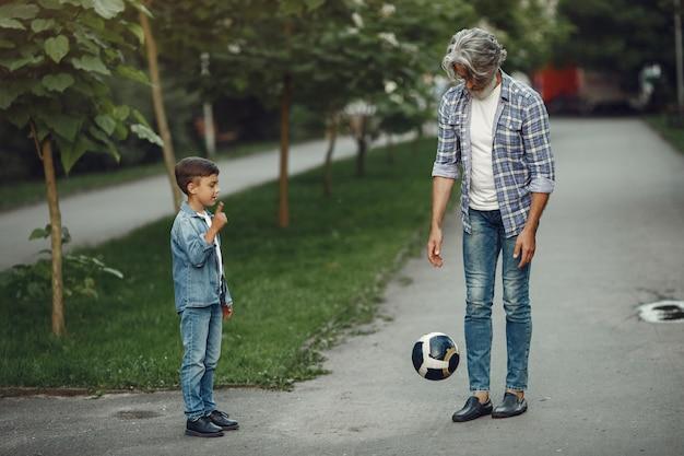 Jongen en grootvader wandelen in het park. oude man speelt met kleinzoon. familie spelen met een bal.