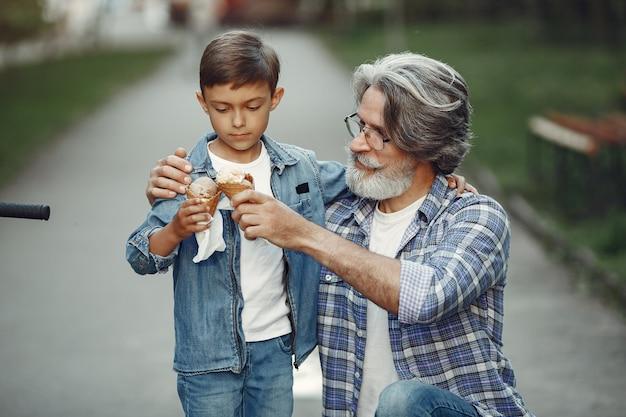 Jongen en grootvader wandelen in het park. oude man speelt met kleinzoon. gezin met ijs.