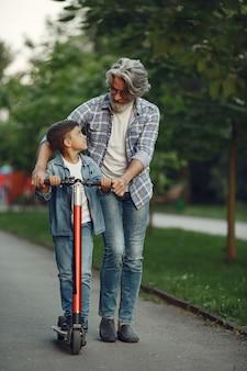 Jongen en grootvader wandelen in het park. oude man speelt met kleinzoon. kind met scooter.