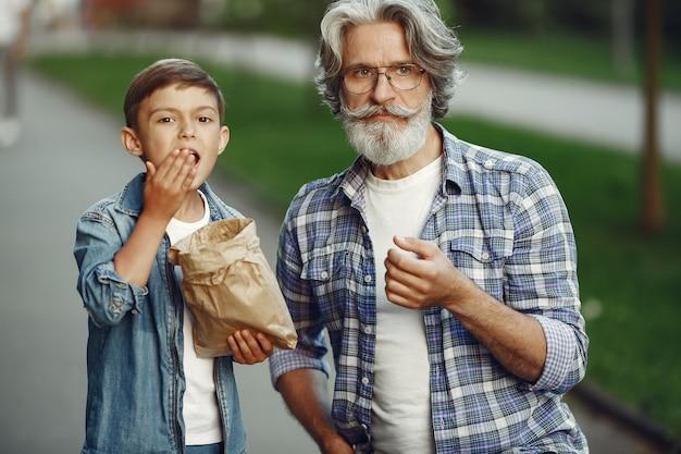 Jongen en grootvader wandelen in het park. oude man speelt met kleinzoon. mensen eten popcorn.