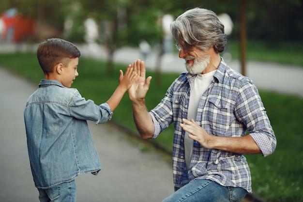 Jongen en grootvader wandelen in het park. oude man speelt met kleinzoon.