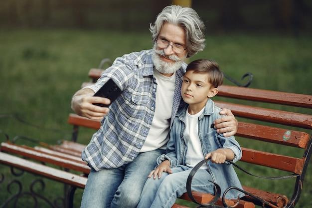 Jongen en grootvader zittend op een bankje. familie in het park. oude man speelt met kleinzoon. grootvader gebruikt een telefoon.