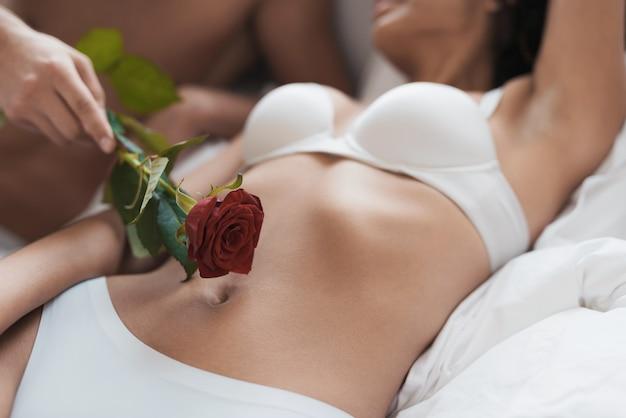 Jongen en het meisje zijn op bed. guy streelt een meisje met roos