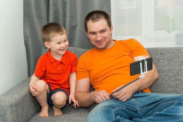 Jongen en man in lichte kleding kijken in de smartphone tijdens online bellen en glimlachen. blijf thuis en communicatieconcept op afstand